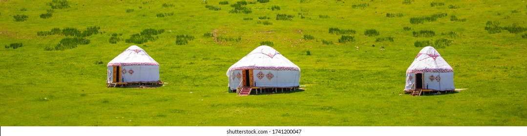 Yurt. National ancient house of the peoples of Kazakhstan and Asian countries. National Housing. Yurts on the background of a green meadow and highlands.
