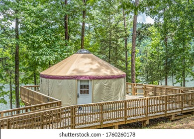 A YURT on a wooden deck in a forest camp ground.