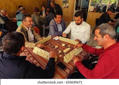 YUSUFELI, ARTVIN PROVINCE, TURKEY - MAY 4: Men sitting around table play the popular tile game Okay in rustic cafe of small village Yusufeli on May 4, 2015.