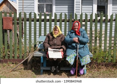 YUZHA, RUSSIA - MAY 4, 2019: Old russian women dressed in russian folk style with newspaper. Rural traditional national wooden house in Yuzha town, Ivanovo oblast, Russia. Lifestyle in countryside