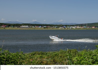 Yuzhno-Sakhalinsk, Russia-August 27, 2019. 3 men and a woman moving on a speedboat on the dust Krasnoarmeyskaya near the village of Okhotskoe.