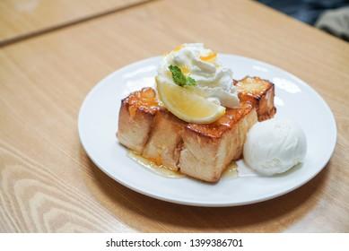 Yuzu honey toast. A cube toast topped with yuzu orange jam/sauce, served with yogurt ice cream, whipped cream and slice yuzu fruit. On white plate, wooden table. (Isolated)