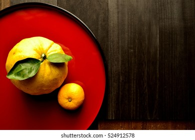 "Yuzu ""Japanese citron"" on red Japanese lacquer ware tray."