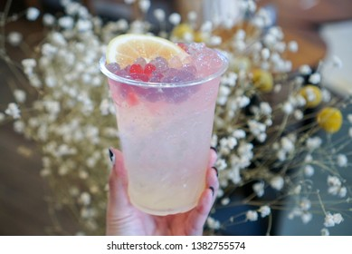Yuzu Soda. Hand holding a plastic cup of yuzu soda with topping colourful konjac jelly and orange peel. (center)