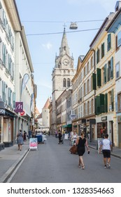 Yverdon-les-Bains, Switzerland - 5.Sept. 2018: Colorful townhouses and church tower are visible along the street in the Old Town. Various stores and people can be seen - Image