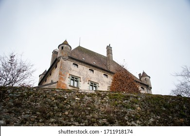 Yvoire, France - December, 2018: Rustic scene, low angle view of a Yvoire Castle  visible above the city walls, with a cold grey sky background. Yvoire is a 700 year old, famous medieval village