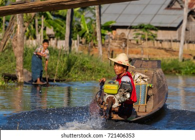 Ywama, Shan State, Myanmar - November 23, 2014: Young men driving one of the many small motor boats used for all traffic and transport purposes at the Inle Lake area.