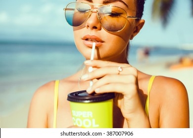 yyoung beautiful brunette girl in sunglasses with beautiful skin and lips, posing on the beach, drinking fresh morning smoothies, fruit juice,cocktail fashion outdoor, close up, cute, , pretty woman