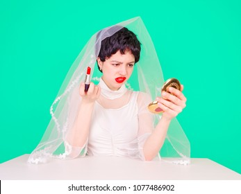YYoung enraged bride teenager looking at her hairstyle in a Mirror sitting at table isolated on light background