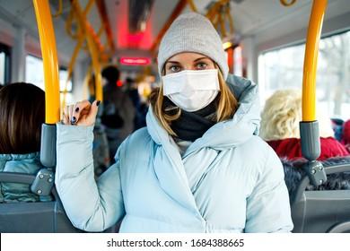 Junge Frau in medizinischer Maske, die nachmittags in der Buslounge neben gelben Handläufen steht.