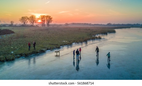 Zaamslag, The Netherlands - January 22, 2017: Two young families and their dog test out the fresh ice on the Otheensche Kreek during sunset in Zaamslag, Zeeuws Vlaanderen, The Netherlands