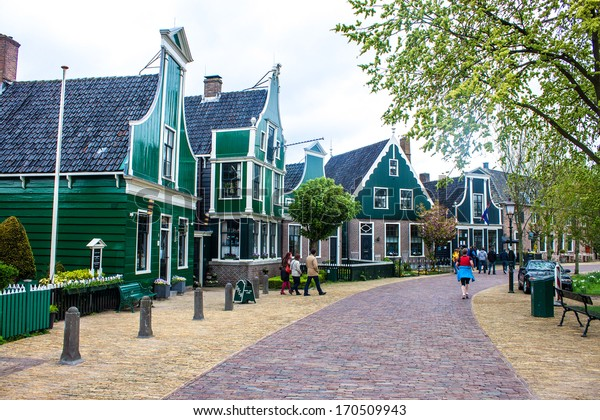 ZAANDAM, HOLLAND - MAY 11: People visit old traditional houses at Zaanse Schans on May 11, 2013 in Zaandam. Zaanse Schans is a collection of well-preserved historic windmills and houses.