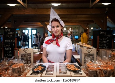 ZAANDAM - JULY 28: Dutch girl selling famous Dutch waffle in a shop at the Zaanse Schans on 28 June, 2018 in the Netherlands. Dutch waffle is a famous product along with Dutch Gouda and Edam  cheese.