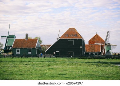 ZAANDAM, THE NETHERLANDS - CIRCA APRIL 2017: Windmill and houses in Zaanse Schans, a neighborhood with well-preserved historic windmills and houses in Zaandam, the Netherlands.