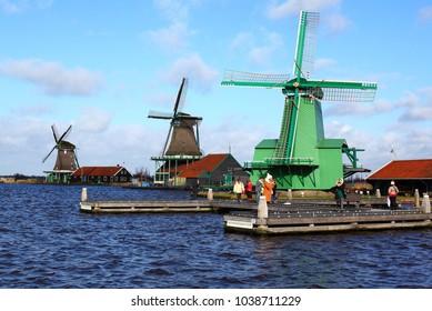 ZAANDAM, THE NETHERLANDS – FEBRUARY 11, 2018: people take pictures near wind mills in Zaandam village, Zaanse Schans, the Netherlands. Wooden mill, world heritage