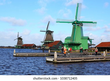 ZAANDAM, THE NETHERLANDS – FEBRUARY 11, 2018: people take pictures near wind mills in the Netherlands. Wooden mill, world heritage