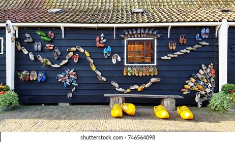 ZAANSE SCHANS - AUGUST 2017: Wooden Shoes wall on August 28, 2017 in Zaanse Schans. This wall of the Wooden Shoes museum is a famous spot for photo opportunity in Zaanse Schans, the Netherlands.