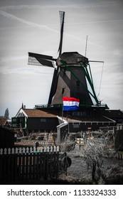 Zaanse Schans, Netherlands, Apr 2015: Windmill and Dutch flag in the village of Zaanse Schans, near Amsterdam, Netherlands