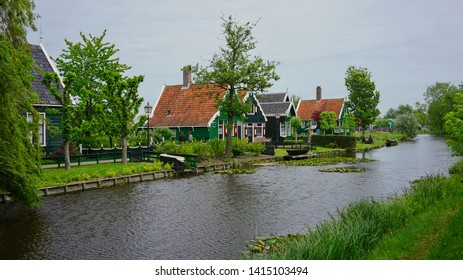 Zaanse Schans, Netherlands - May 24 2019:  An old Dutch town with green wooden houses in Zaanse Schans by the canal.