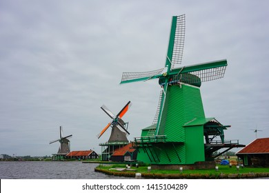 Zaanse Schans, Netherlands - May 24 2019:  Old windmill houses in Zaanse Schans village by the river near Zanndam.