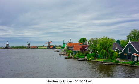 Zaanse Schans, Netherlands - May 24 2019:  Old historic windmills and green wooden houses by the Zaan river near Zaandam.