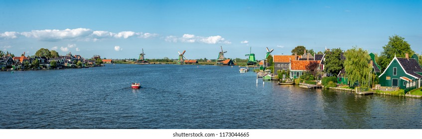 Zaanse Schans, North Holland / The Netherlands - September 2 2018: A view of the historic Zaanse Schans windmills and neighborhood near Zaandam. Bright, sunny day, with a boat on the river.