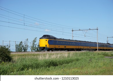 Zaanstad/Netherlands, june 07, 2015: A train of the Dutch National Railway in the meadows of Noord-Holland