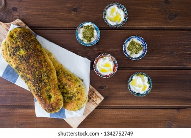 za'atar bread, a lebanese or turkish or arabic bread made with sumac, sesame  seeds  olive oil served with labneh or labane on top on wooden brown plate background , flatlay top view with copy space