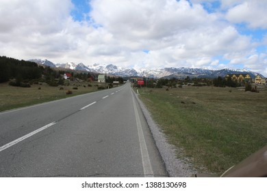 Zabljak, Montenegro - 4/28/2019: Panoramic view with old houses and road from the beautiful green plateau of Zabljak mountain to the snowy Durmitor mountain, Montenegro