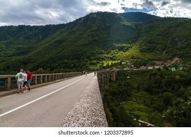 """Zabljak/Montenegro - September 2018: People at Tara Bridge. Tara Canyon. """"Durdevica Tara Bridge"""" - concrete Tara Bridge in north Montenegro."""