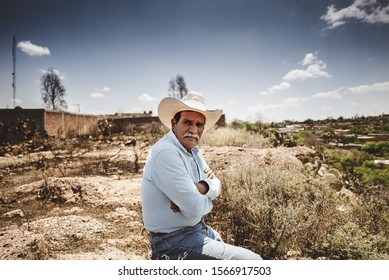 ZACATECAS, MEXICO - Nov 11, 2019: Shot of an Old Mexican Cowboy sitting on a rock with denim shirt in the desert