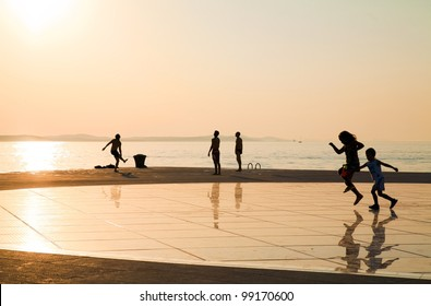 """ZADAR - AUGUST 27: Silhouetted children play at  sunset  over Adriatic sea  on solar panel urban installation """"Greeting to the Sun""""  by architect NIcola Basic, August 27, 2012, in Zadar, Croatia"""