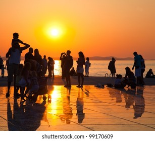 """ZADAR - AUGUST 27: Silhouetted people watch sunset  over Adriatic sea  on circular solar panel urban installation """"Greeting to the Sun""""  by architect NIcola Basic, August 27, 2012, in Zadar, Croatia"""
