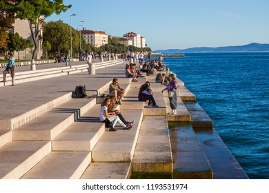 Zadar, Croatia - 07 October, 2010: People relax at the Sea Organ at sunset, experimental musical instrument, which plays music generated by the motion of sea waves of the Adriatic Sea, city landmark.
