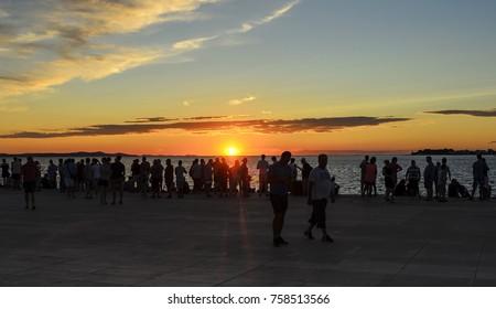 ZADAR, CROATIA - 15 JULY, 2017: People admire the sunset on the beach
