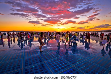 ZADAR, CROATIA - July 18 2017:  Unidentified people in city of Zadar Greetings to the sun landmark in region of Dalmatia, Croatia at  sunset. Many tourists visits this solar powered installationon sea