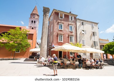 ZADAR, CROATIA - MAY 27, 2017: Unidentified traveler women reading a map in front of restaurant at old city on blue sky background.Famous tourism location in Europe,Croatia.Landmark of the world.