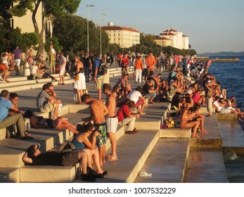 Zadar, Croatia - September 4, 2013 : People|tourists relaxing at sunset and enjoying the music of sea organ in Zadar