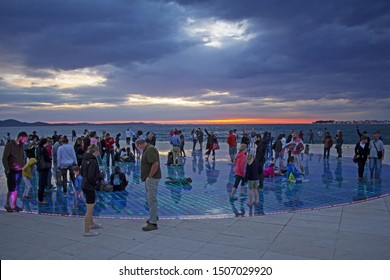 "ZADAR/CROATIA - JULY 16: Many people watch sunset over Adriatic sea on famous solar panel urban installation ""Greeting to the Sun"", July 16, 2016, in Zadar, Croatia"