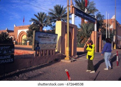 ZAGORA, MOROCCO - OCT 15, 2000 - Tourist taking picture of sign to Timbuktu, Zagora, Morocco