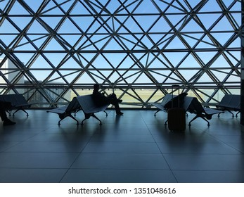 ZAGREB AIRPORT - 24 MARCH 2019: Passenger waiting in departure lounge on bench in front of large window as a silhouette.