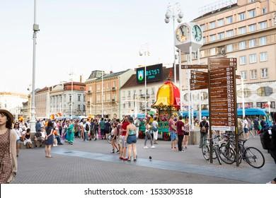 ZAGREB, CROATIA - 10th August, 2019. A scene of busy Ban Jelacic main Square (Trg bana Jelacica) in Zagreb, Croatia. White clock, street indicators, tourists and Krishna devotees chariot.