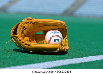 ZAGREB , CROATIA - 13 AUGUST 2015 -  official Major League Baseball ball and glove on the green field , product shot