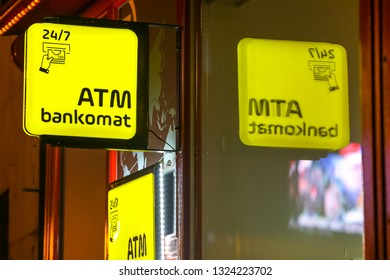 Zagreb, Croatia - 29th, December 2018 : Close up of Atm machine yellow sign on the street during night in Zagreb, Croatia.