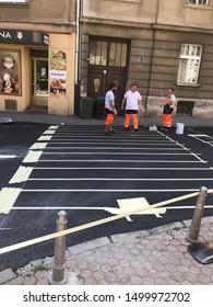 ZAGREB, CROATIA - 8 AUGUST 2019: Road workers making zebra crossing lines on road.