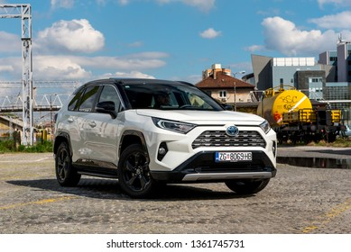 ZAGREB, CROATIA - APRIL 06, 2019: New Toyota RAV 4 Hybrid. Modern SUV transport vehicle in urban environment with blue sky in background. White Toyota car with new Hybrid technology.