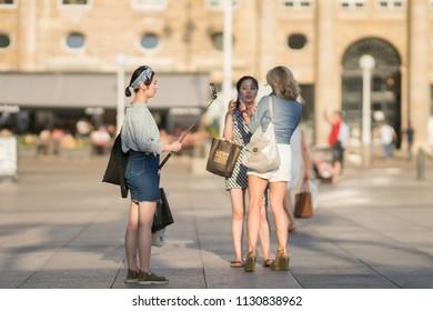 ZAGREB, CROATIA - AUGUST 4, 2017: Asian tourist taking selfie on Ban Josip Jelacic square.