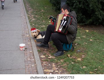 Zagreb, Croatia, December 2, 2018: Busking accordion player with his dog wearing a hat on the street of Zagreb during the annual Advent Market