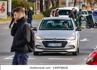 Zagreb, Croatia - January 17, 2019: A driver is talking on a mobile phone waiting at the traffic light making a misdemeanor while young man is crossing the street also talking on a mobile phone.