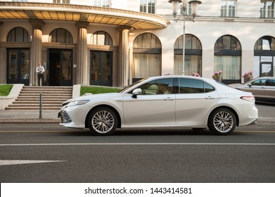 ZAGREB, CROATIA - July 05, 2019: New Toyota Camry in white colour. Luxury business limousine cruising the streets. Toyota luxury model in front of a hotel.